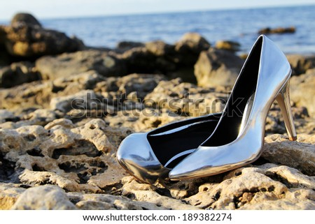 Close-up shot of Pair of Silver High Heel Shoes on yellow stones near sea  - stock photo