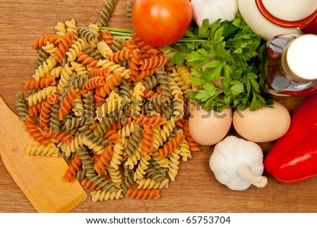 Close-up shot of pasta and vegetables on wooden board. Studio shot - stock photo