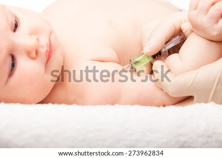 Close-up shot of pediatrician giving a three month baby girl  intramuscular injection in arm - stock photo