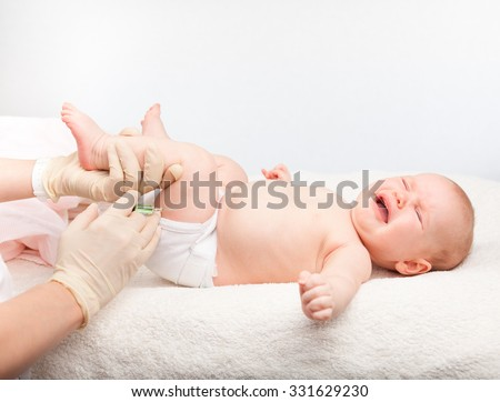 Close-up shot of pediatrician giving a three month baby girl  intramuscular injection in leg - stock photo