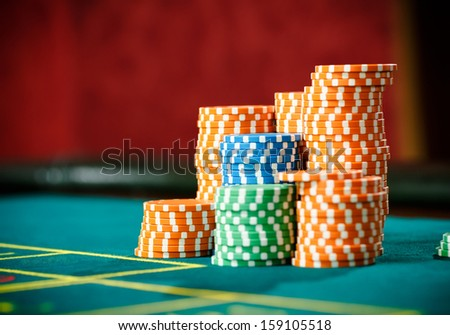 Close up shot of piles of chips on the roulette table. Symbol of addiction to the gambling - stock photo