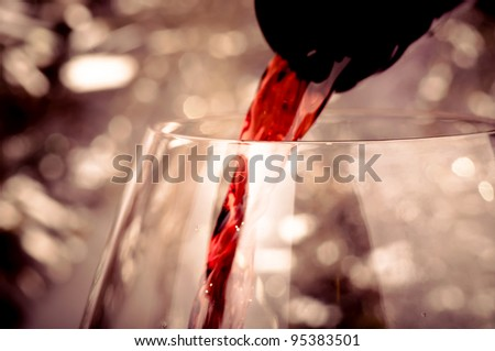 Close-up shot of pouring red wine into glass - stock photo