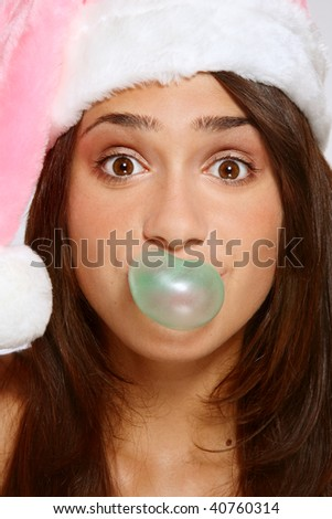 Close-up shot of pretty young grimacing girl in pink Santa hat blowing green bubble-gum