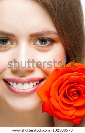 Close-up shot of pretty young woman with beautiful fresh make-up and perfect healthy skin with rose - stock photo