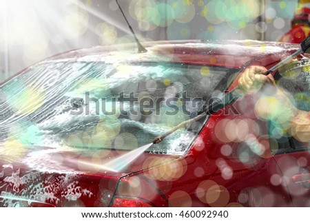 close up shot of red car being washed with pressure washer.