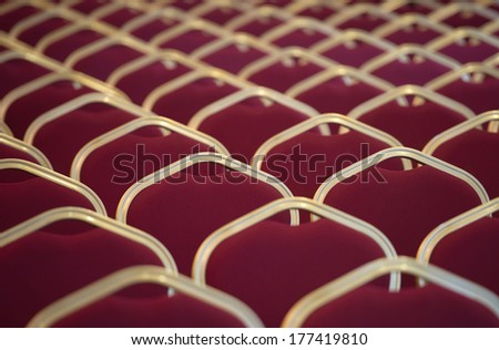 Close-up shot of red chair seats in empty conference room - stock photo