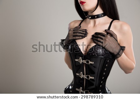 Close-up shot of sexy woman in black fetish corset and bra, studio shot