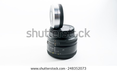 Close up shot of silver metallic color of mini compact interchangeable lens for small compact mirrorless or dslr camera gear versus standard DSLR lens or full frame lens. Isolated on white background.