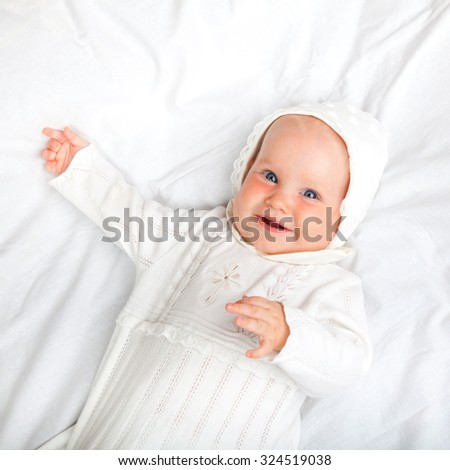 Close-up shot of six month baby girl wearing white christening clothes laying on a bed smiling - stock photo