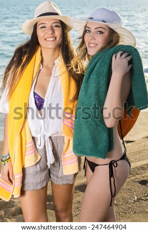 Close up Shot of Smiling Pretty Young Girls Posing with their Towels at the Beach While Looking at the Camera - stock photo