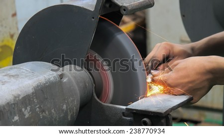 Close up shot of sparks from grinding wheel.metalworking industry: finishing metal working on surface grinder machine with flying sparks