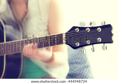 close up shot of strings and guitarist hands playing guitar - stock photo