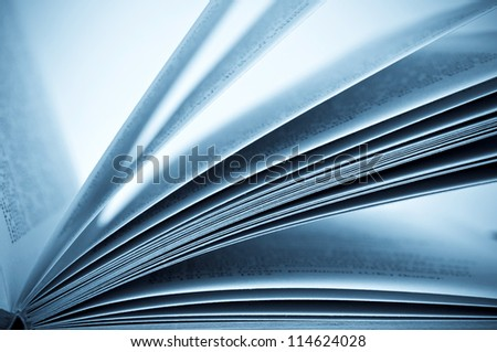Close-up shot of the open book - blue toned image - stock photo