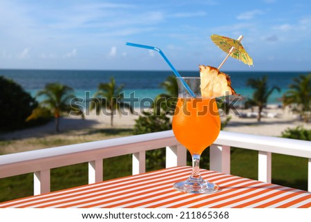 Close-up shot of the orange drink on the beach, sea and sky background - stock photo
