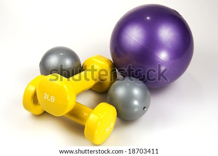 Close up shot of three medicine balls and two lifting weights