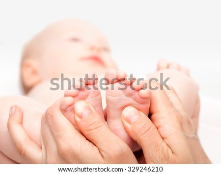 Close-up shot of three month baby girl receiving foot massage from a female massage therapist. Camera is focused on infant's feet. Face is blurred in background. - stock photo
