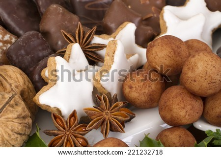 Close up shot of traditional German christmas cookies, such as Aachener Printen, Marzipankartoffeln, Zimtsterne and iced gingerbread decorated with evergreens and walnuts. - stock photo