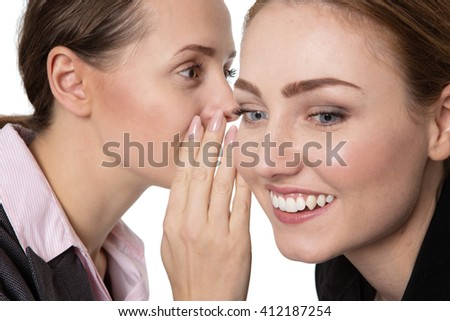 Close up shot of two happy, pretty business women, sharing a secret and whispering in each others ear.