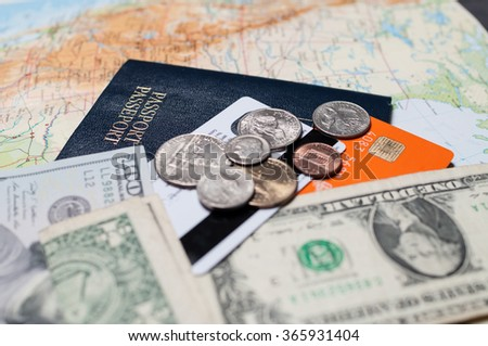 Close up shot of US currency with passport and credit cards, with a map for a background. Business travel and tourism concept