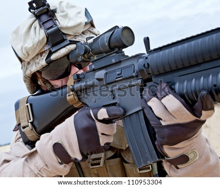 Close-up shot of US marine shooting his rifle - stock photo