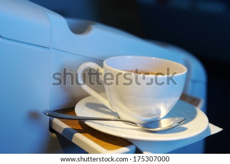 close up shot of white cup with hot tea in business class of airplane. focus on handle - stock photo