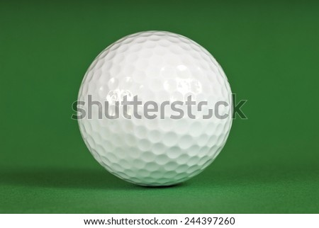 Close Up Shot Of White Golf Ball On Green Background - stock photo