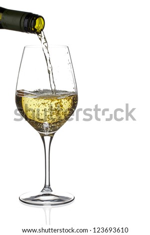 Close-up shot of white wine being poured in glass - stock photo