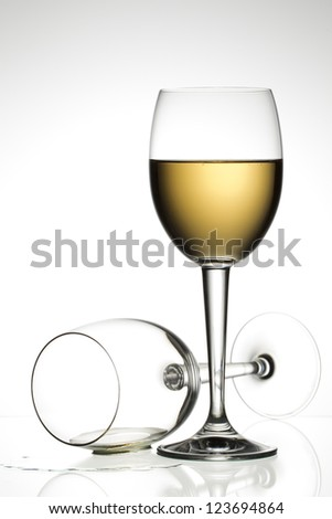 Close-up shot of white wineglass against plain white background. - stock photo