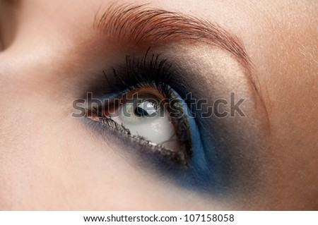 Close-up shot of woman eye with beautiful blue makeup looking away - stock photo