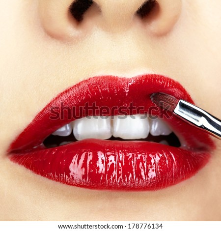 Close-up shot of woman face and makeup brush  applying red lipstick make-up on lips - stock photo