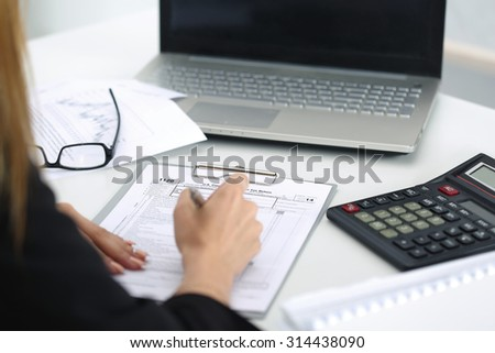 Close up shot of woman hand filling tax form. Savings, finances and economy concept - stock photo