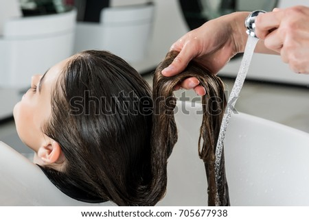 close-up shot of woman having hair wash in beauty salon