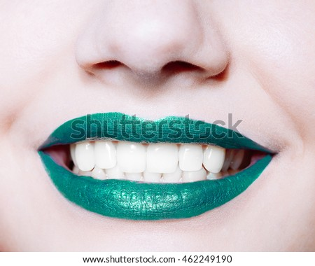 Close-up shot of  woman lips with glossy green  lipstick