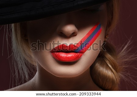 Close-up shot of woman lips with glossy red lipstick