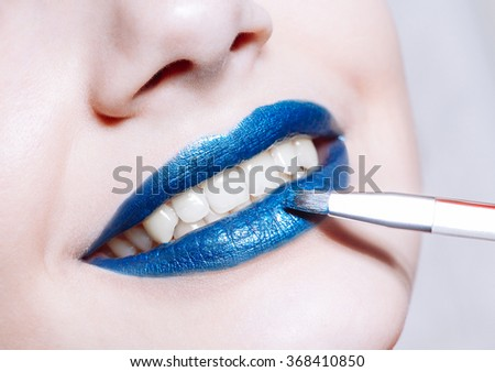 Close-up shot of  woman paints her lips with glossy blue lipstick - stock photo