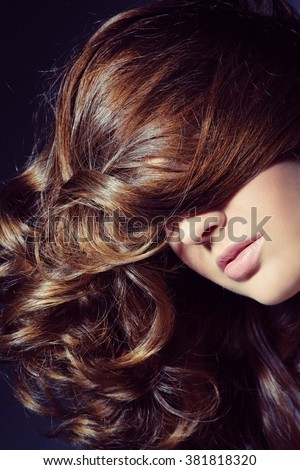 Close-up shot of woman with long curly hair, selective focus