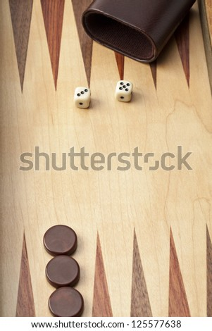 Close-up shot of wooden backgammon board with dices and brown pieces with cup. - stock photo
