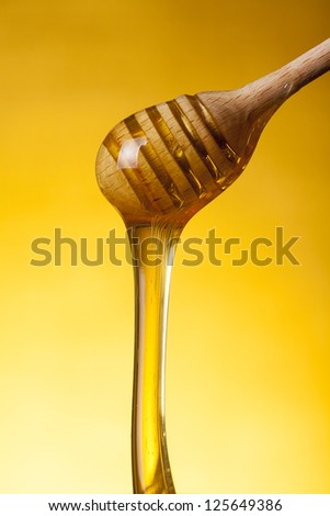 Close-up shot of wooden drizzler and flowing honey over yellow background