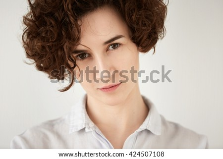 Close up shot of young brunette Caucasian woman looking with serious expression at the camera. Portrait of displeased or angry female office worker posing against white concrete wall background  - stock photo