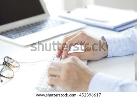 Close-up shot of young businessman's hand while typing on computer's keyboard.
