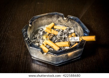 Close up shot to a cigarette left in the astray on wooden table - stock photo