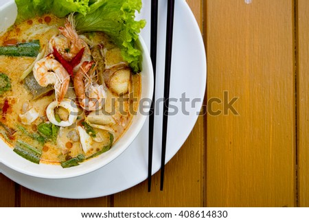 Close up shot Tom yam kung thai cuisine and dry chilly on colorful soup and spicy on yellow wooden background - stock photo