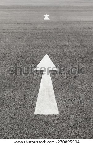 Close up shot White arrow sign on asphalt ground - stock photo