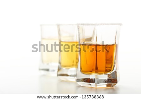 close up shot with tequila or rum in glass on white background