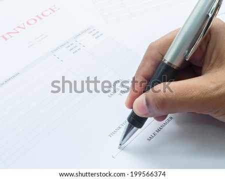 Close up showing fingers  holding a pen to sign on  invoice document