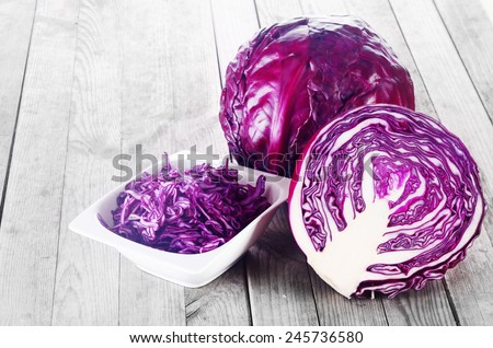 Close up Shredded, Sliced and a Whole of Purple Cabbage Vegetable on Top of Wooden Table - stock photo