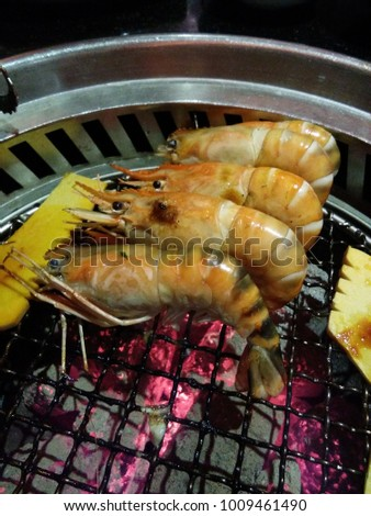 close up,  Shrimp is placed on a charcoal grill. There is a pumpkin cut near, shrimp is cooked to eat a beautiful orange.Thai seafood