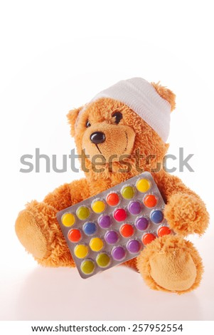 Close up Sick Plush Teddy Bear with Bandage on the Head Holding a Foil Packaged Colored Pills, Isolated on White Background. - stock photo