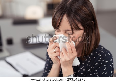 Close up Sick Young Office Lady at her Desk Sneezing Into a White Tissue with Eyes Closed. - stock photo