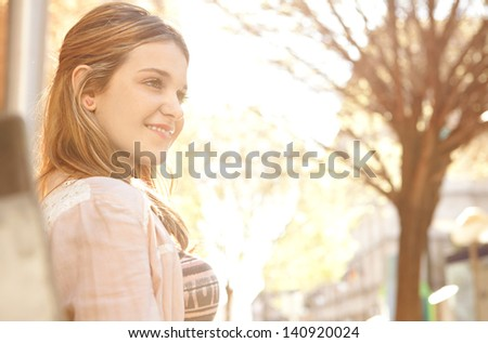 Close up side portrait of a young teenager girl sitting on a bench in the city center, looking ahead with the warm sun shining through with golden light. - stock photo
